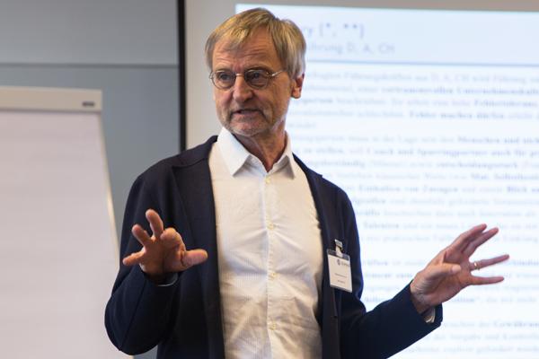 Wolfgang Zimmermann spricht stehend vor den Workshopteilnehmer_innen