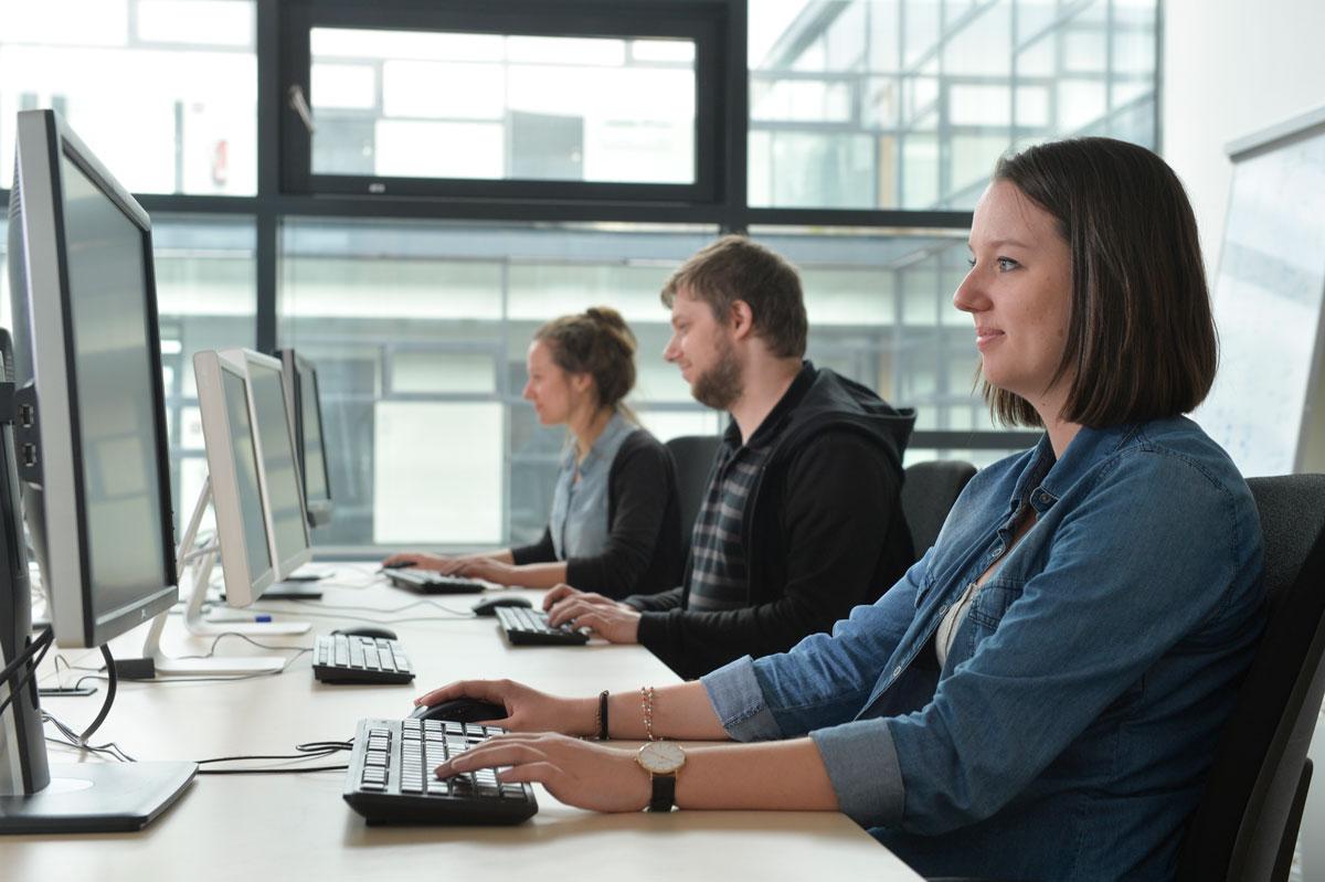 Drei Personen an Computern