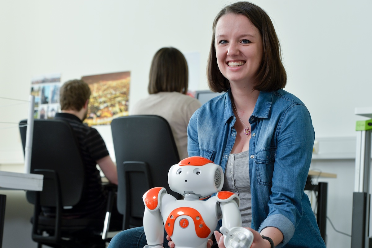 Im Hintergrund sitzen zwei Personen an Computern, im Vordergrund ist eine Frau mit Roboter zu sehen.