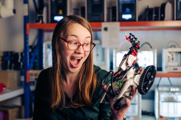 Junge Frau betrachtet ein technisches Objekt mit staunend-amüsierten Gesichtsausdruck
