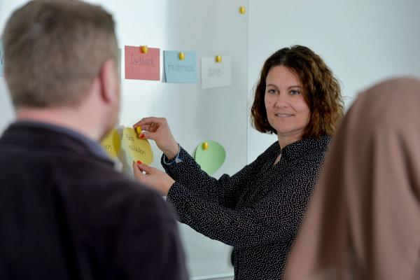 Frau steht vor einer Magnettafel und pinnt eine Karte an. Dabei schauen ihr zwei Personen zu.