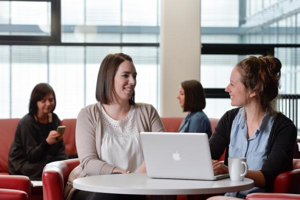 Zwei Frauen sitzen im Hintergrund auf einem Sofa, im Vordergrund sitzen zwei Frauen zu einer Besprechung an einem runden Tisch, auf dem ein aufgeklappter Rechner steht.