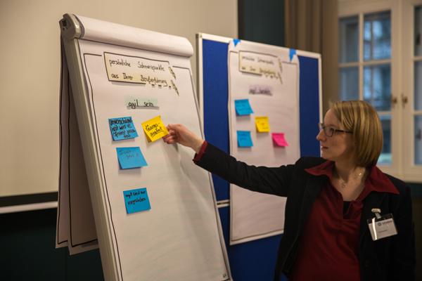 Workshopleiterin Ruth Steinseifer heftet eine Notiz an ein Flipchart